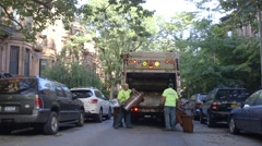 Sanitation workers collecting garbage in garbage truck - stock footage