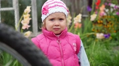 Small girl frowning and confused in the garden in slowmotion. 1920x1080 Stock Footage