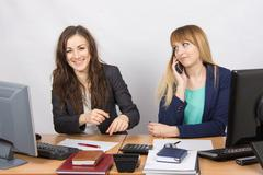 Two young beautiful girls colleagues sitting at the same desk in the office Stock Photos