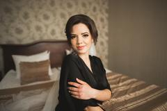 Luxury bride in black robe posing while preparing for the wedding ceremony - stock photo