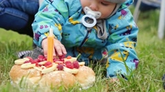 Little boy tries to take cake on his first birthday in the park in slowmotion Stock Footage