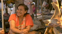 An asian woman vender smiles while selling meat and pig legs Stock Footage