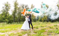 Wedding couple with color smoke in the summer park - stock photo