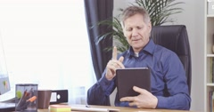 Man with grey hair working with tablet computer and have an idea - stock footage
