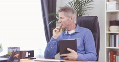 Man with grey hair working with his tablet computer at home office Stock Footage