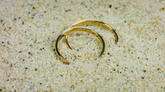 Wedding gold rings in white sand on tropical beach. Closeup rotation. Stock Footage
