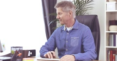 Man with grey hair working at his computer on desk in a home office - stock footage