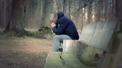 Lonely, depressed man in the park - stock footage