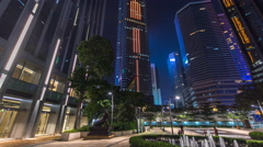 Night view hyperlapse of modern city in park with fountain and skyscrapers - stock footage