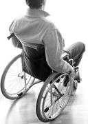 disabled sitting in a wheelchair in the room near the window - stock photo