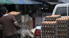 A man carries crates of eggs from the back of his pickup truck into a market Stock Footage