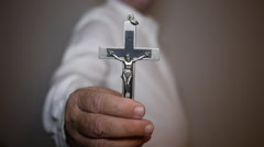 Man holds up a Christian cross crucifix. Stock Footage