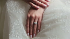 Beautiful brunette bride sits with folded arms and softly looks on camera Stock Footage