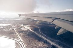 Aircraft wing over winter snow landscape with trees and highways Stock Photos