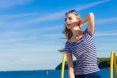 Girl enjoying summer breeze sky background Stock Photos
