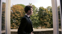 Handsome groom dreamily  looks through a window Stock Footage