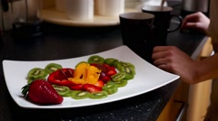 Plate with colorful fruits. Girl take one slice of the strowberry. Close up Stock Footage