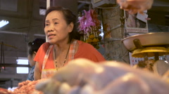 Low angle shot of a vendor helping a customer racking from chicken to woman Stock Footage