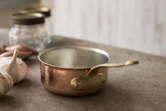 Empty Copper Saucepan Beside Garlic, Shallots, and Jars Stock Photos