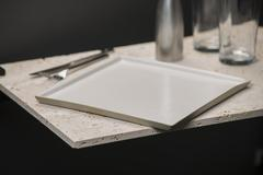 White, Square Dining Plate with Glasses, Knife, and Fork - stock photo