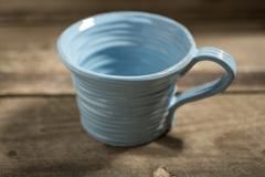 Blue Teacup on a Wooden Surface - stock photo