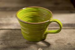 Green Teacup on a Wooden Surface - stock photo