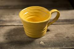 Yellow Teacup on a Wooden Surface - stock photo