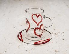Crystal Cup and Saucer with Red Hearts Design on Stone Surface Stock Photos