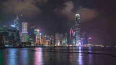 Hong Kong city skyline at night over Victoria Harbor with cloudy sky and urban Stock Footage