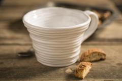 Empty White Teacup Between Spoon and Biscuits Stock Photos