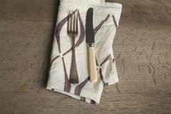 Utensils on Napkin with Brown Concave Lines at High Angle Stock Photos