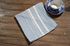 Blue Dinner Napkin with White Bands Alongside Porcelain Teacup Stock Photos
