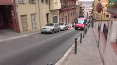 Narrow urban street at hill, look downwards steep roadway slope Stock Footage