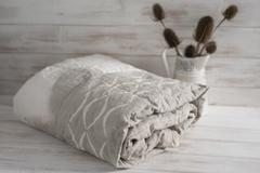 Rolled Two-Tone White and Gray Duvet with Thistle Plants Stock Photos