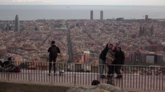 Young friends take group selfie against Barcelona cityscape, stand at edge Stock Footage