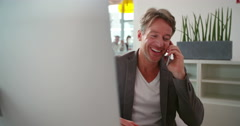 Mature business man talking on smartphone at desk Stock Footage