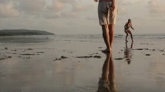 Young friends playing frisbee on beach Stock Footage