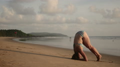 Young fit girl doing headstand on beach Stock Footage