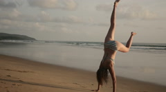 Strong woman doing handstand on beach - stock footage
