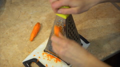 Female Hand Rubs Carrots Grated - stock footage
