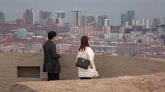 Asian couple at observation deck against blurred cityscape, telephoto view Stock Footage