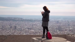 Asian girl with smartphone stand against aerial city, quickly look to camera Stock Footage