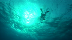 Scuba diver swims at sunlight - underwater silhouette shot Stock Footage
