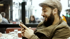 4k hip stylish man in cafe texts on smartphone laughs enjoys himself Stock Footage