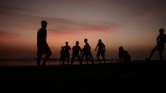 Boys playing on beach during sunset Stock Footage