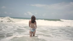 Half naked woman from behind in ocean waves - stock footage