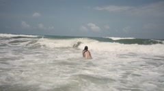 Half naked woman jumps into ocean waves - stock footage