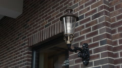The Old Wrought-Iron Lamp on a Brick Wall Stock Footage