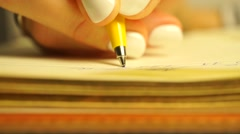 Young woman writing several lines in her planner. Macro video of handwriting Stock Footage