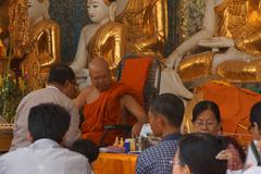Visitors consult a Buddhist monk - stock photo
